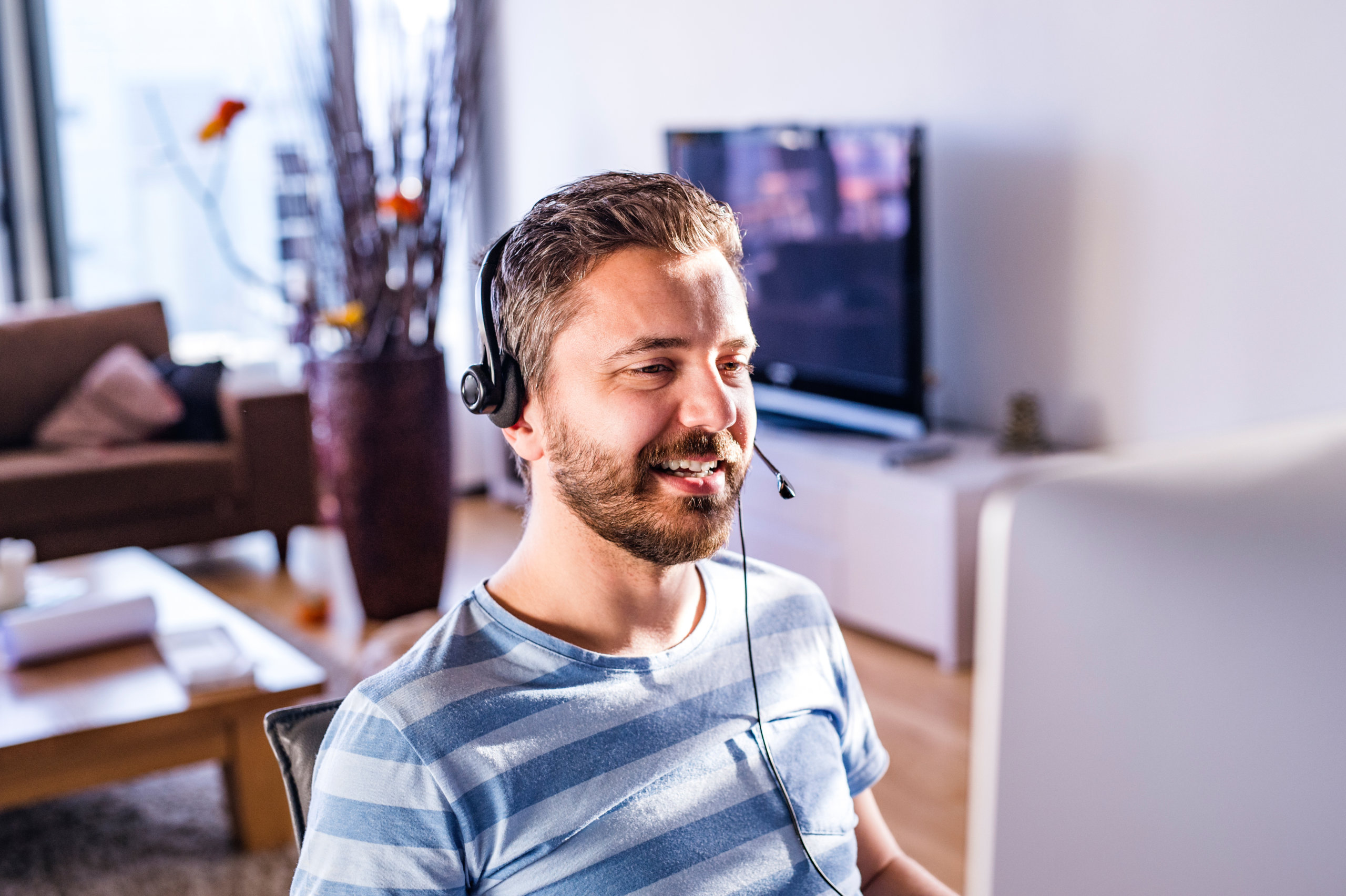 Man sitting at the desk, working from home on computer, wearing headseat, talking on the phone